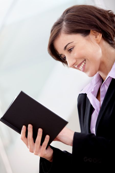 Business woman at the office reading a book and smiling