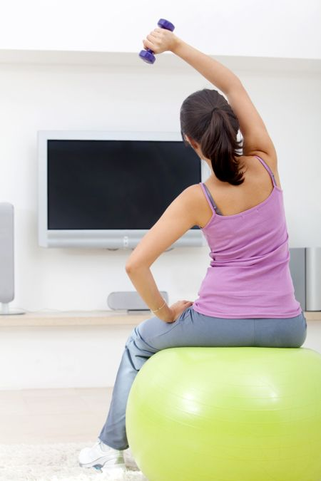 Woman exercising at home in front of the tv