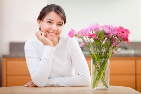 Beautiful woman next to a bunch of  flowers and smiling - indoors