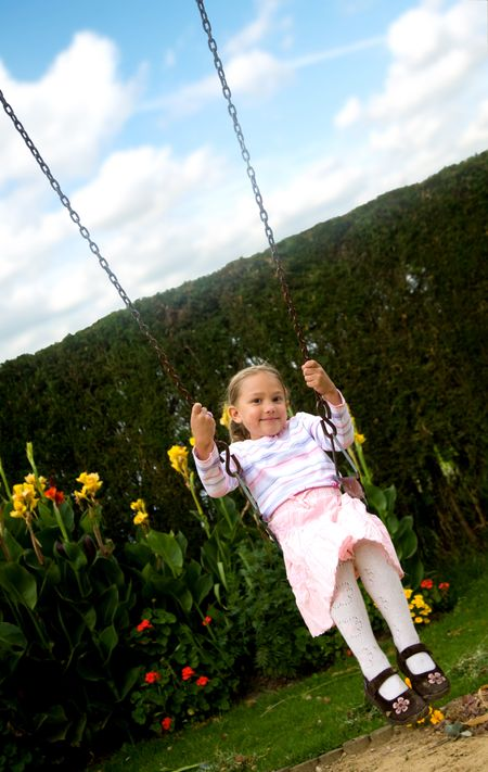 happy girl on a swing in a children playground