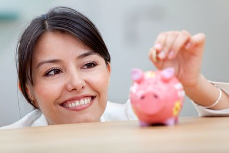 Business woman putting a coin into a piggybank and smiling