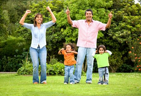 happy family portrait outdoors having fun jumping around