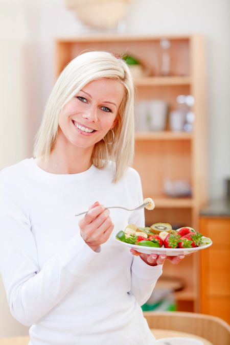 Healthy woman eating fruits at home and smiling