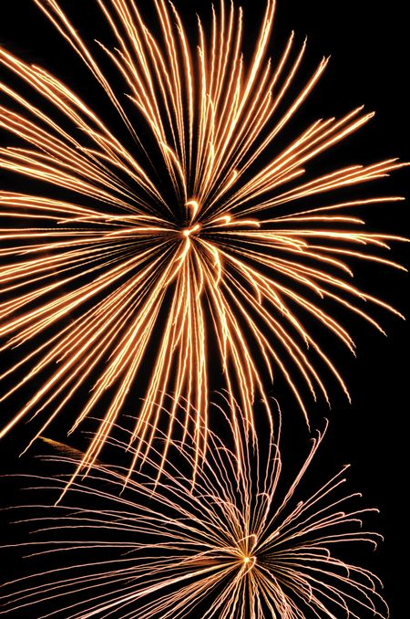 Two bursts of fireworks, the top reddish-yellow, the bottom silver with reddish-orange interior