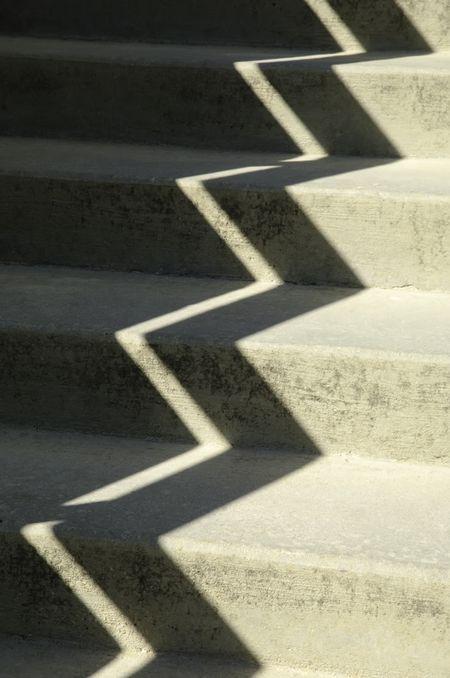 Zigzag shadow on sunlit concrete stairway