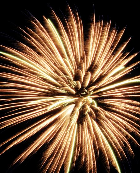 Yellow and orange burst of fireworks with feathery motion blur