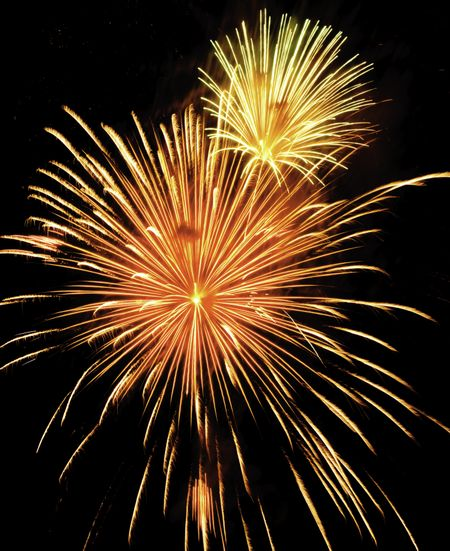 Two bursts of fireworks, the smaller yellow-white, the larger reddish-orange and yellow