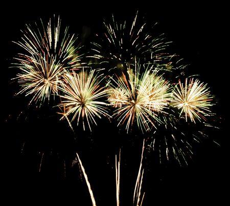 Multiple bursts of fireworks with rocket trails