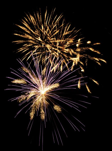 Multiple bursts of fireworks, one blue and white, others golden with motion blur
