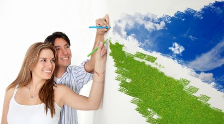 Happy couple drawing a landscape with blue sky and green grass