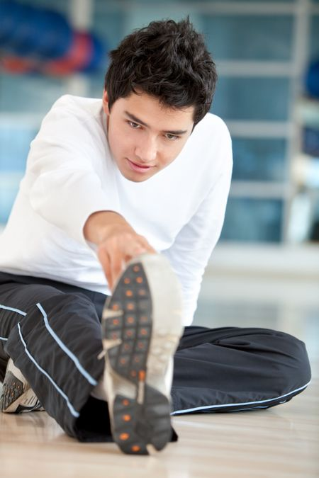 Man doing stretching exercises for his leg at the gym