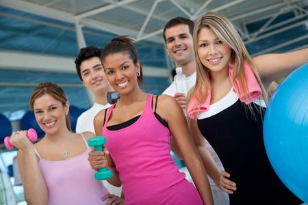 Group of athletic young people at the gym holding free-weights