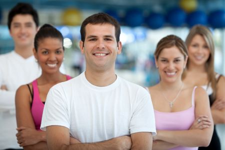 Group of athletic young people at the gym smiling