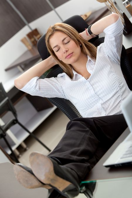 Confident business woman at the office with his feet on the desk