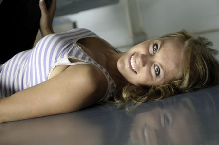 Smiling young Caucasian woman lies on reflective floor of hangar, hand on airplane wheel