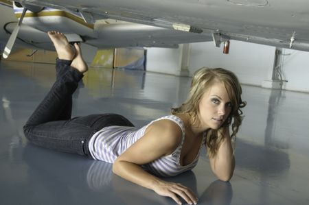 Pretty young Caucasian woman in tank top and blue jeans lies on reflective floor beneath airplane in hangar