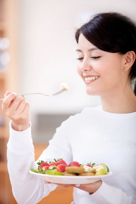 Woman eating with fruits and smiling - healthy lifestyle
