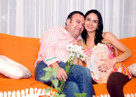 casual couple at home in their sofa - lady is pregnant
