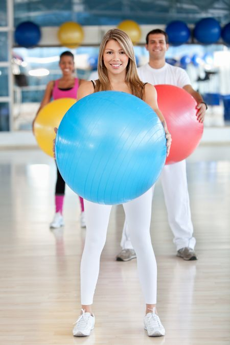 Group of people at the gym smiling with a pilates ball