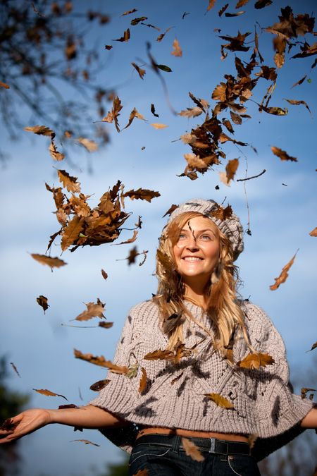 Beautiful autumn woman with leaves falling from the tree