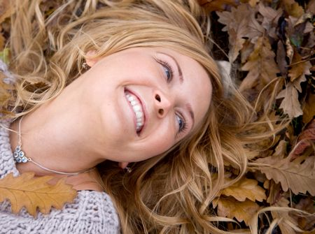 Beautiful autumn woman lying on the floor with leaves around her head