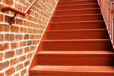 Bottom portion of steel stairway alongside a brick wall