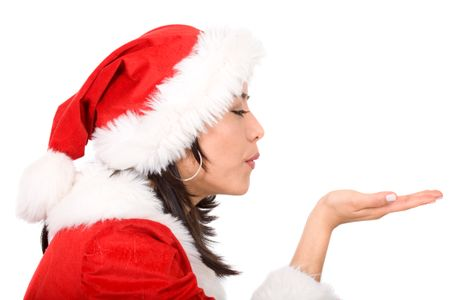 female santa blowing something on her hand isolated over a white background
