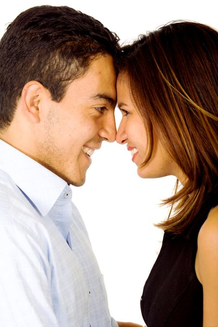 young couple smiling and standing facing each other - isolated over a white background