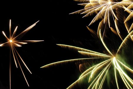 Bursts of fireworks with white-hot cores and reddish-orange, greenish, and white streaks with feathery motion blur