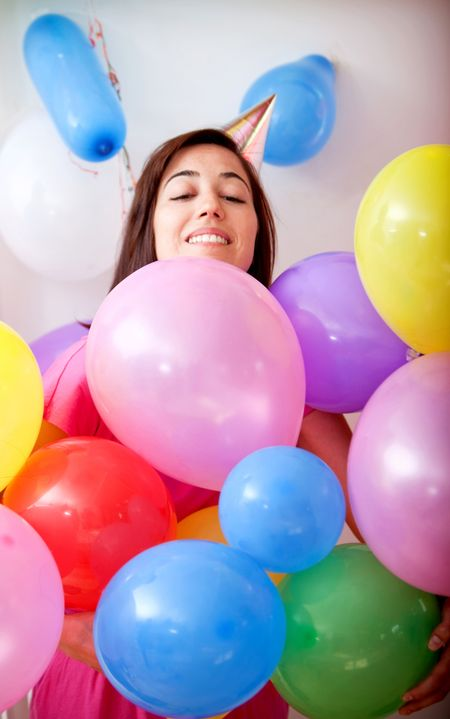 Beautiful girl smiling and covered with balloons in a birthday party