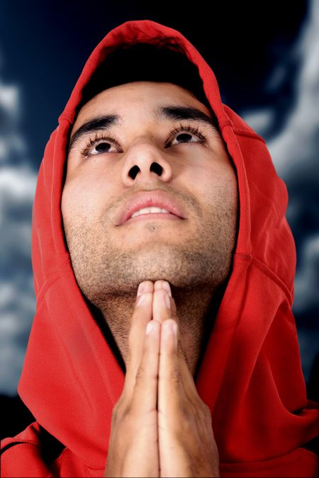 casual guy praying outdoors in a park over a dark sky