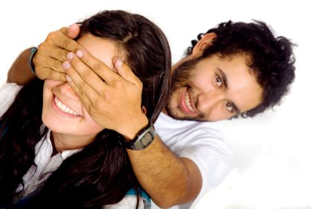 man covering a girls eyes to see if she can guess who is behind her - isolated over a white background