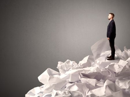 Thoughtful young businessman standing on a pile of crumpled paper with a deep grey background