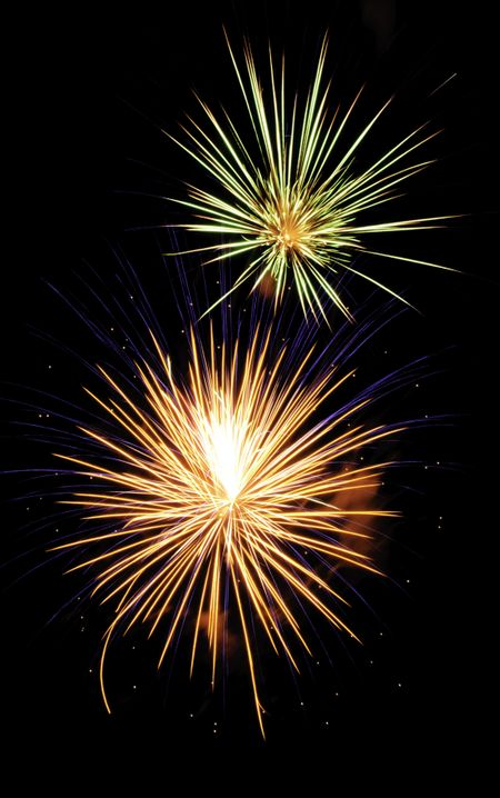 Two bursts of fireworks, the lower burst multicolored and the upper yellow-white