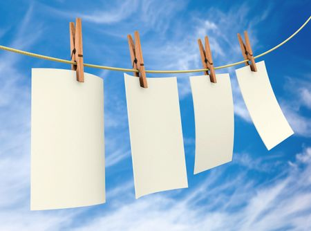 Clothes pin holding white sheets of paper outdoors