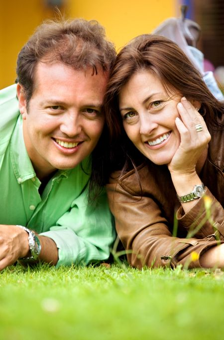 couple portrait on the floor outdoors where both are smiling and looking happy