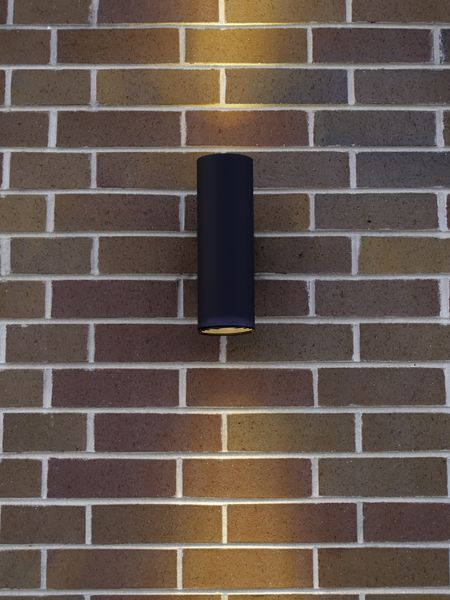 Black cylindrical light fixture on exterior brick wall