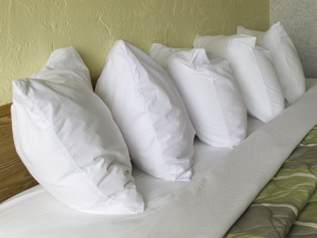 Row of five pillows on hotel bed
