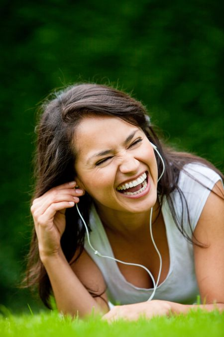 Happy woman lying on grass listening to music outdoors and laughing