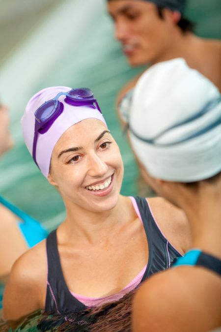 Woman in a swimming pool talking to other people and smiling