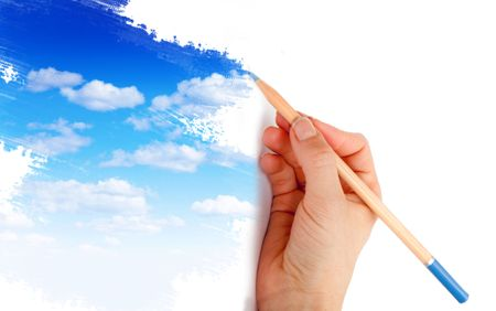 Hand holding a color pencil and drawing a blue sky