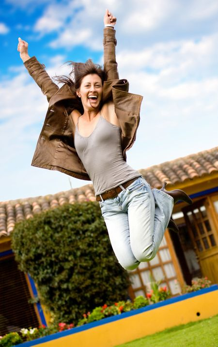 happy girl jumping and smiling portrait outside her home
