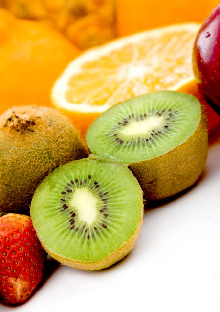 delicious fruit of all kinds isolated over a white background - focus is on kiwi