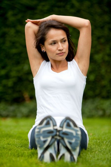 Young woman exercising outdoors stretching one of her arms