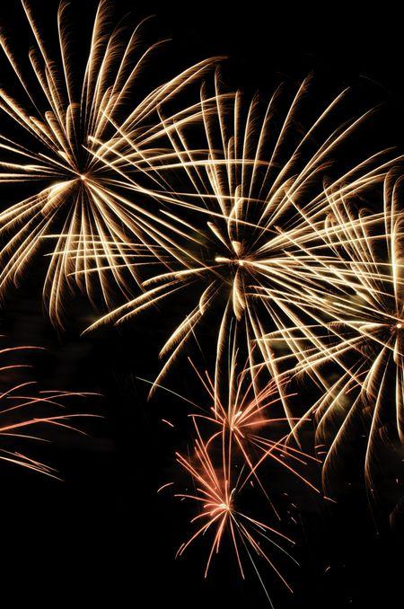 Three similar bursts of yellowish fireworks near smaller bursts