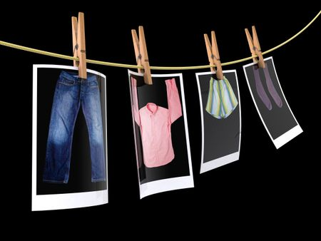 Pin holding photographs of clothes to dry - isolated over a black background