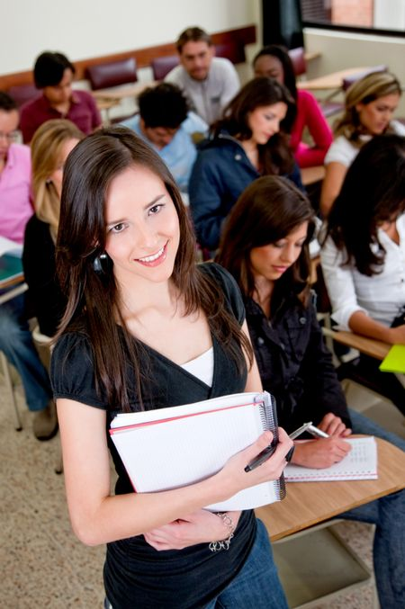 Female student in the classroom with a notebook and smiling