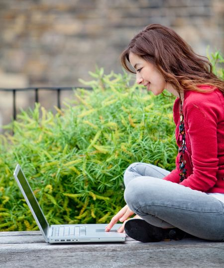 Young woman working on a laptop computer outdoors
