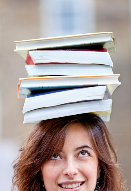 Woman carrying books on her head and trying to balance them