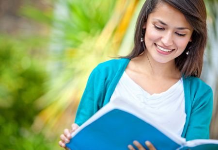 Beautiful girl studying outdoors reading a book